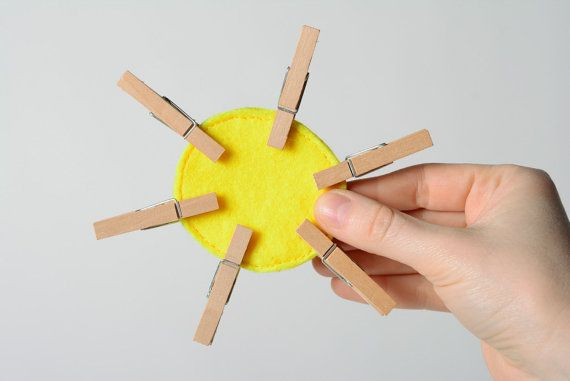 Bright yellow handmade educational toy sewn of felt with clothes pins Sun
