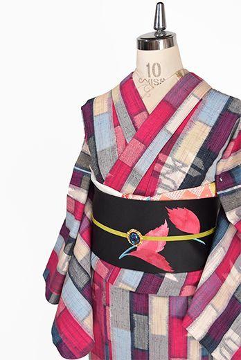 鮮やかなフーシャピンクも印象的に、スカイブルーやブラック、ベージュ、グラスグリーンの色糸が織り込まれステンドグラスのようなドラマチックな幾何学パターンを描き出すウール単着物です。