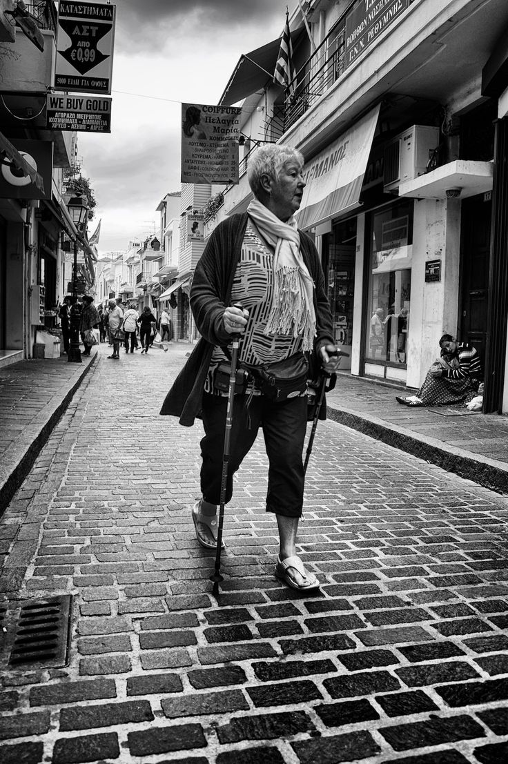 "I never expected to take this photograph. I was walking down the street with my wife and 2 daughters and I had my camera in hand, just in case. I had my 20mm lens on that is great for ""just in case"" days. Anyway, as we were walking I saw this tall lady, walking down the street. She was holding trekking sticks, wearing a belt with a camera and a bag strapped around her waste and was looking at the shop windows. She walked passed that mother and her child on the pavement as if they were ..."