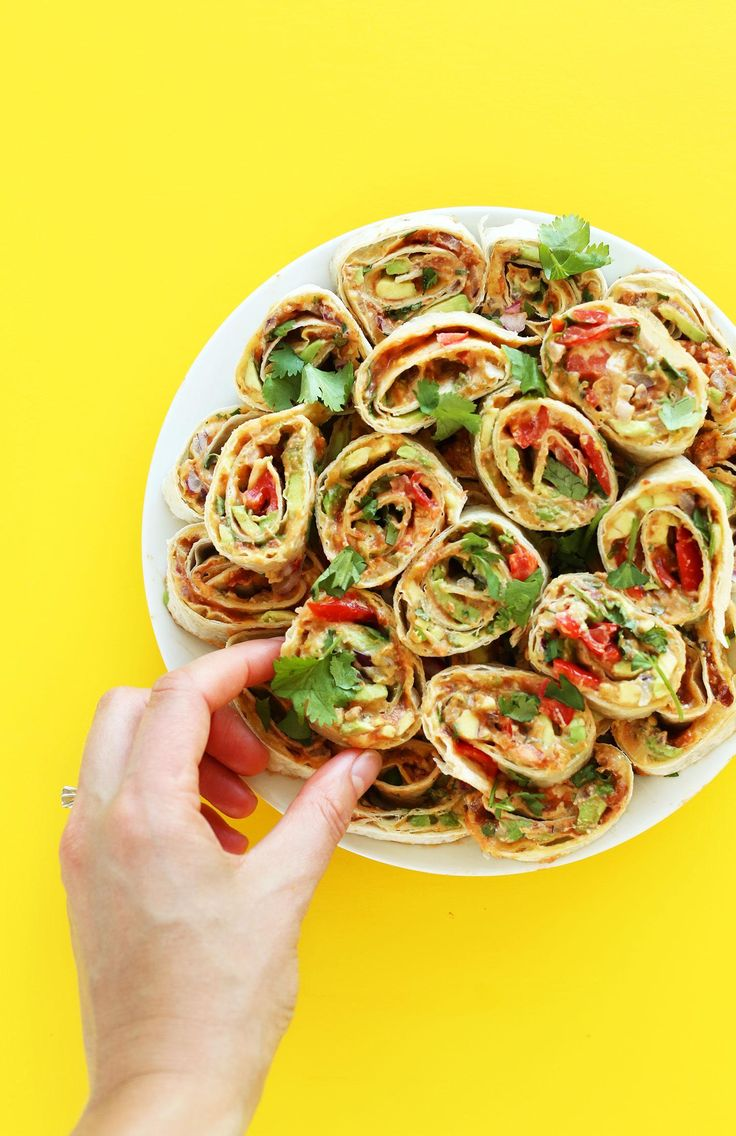 Easy, 6-layer Mexican pinwheels with refried beans, avocado, vegan mexican cheese and more! The perfect savory, satisfying side, snack or appetizer! Ingredients 2 large vegan flour tortillas optional: 2/3 cup Spreadable Vegan Mexican Cheese, divided 2/3 cup (158 g) vegan refried beans (I love Trader Joe's brand), divided 1/2 ripe avocado, finely sliced or diced, divided 1/2 cup (80 g) red onion, finely diced, divided 1/2 cup (75 g) finely diced tomato or chunky salsa, excess liquid drai