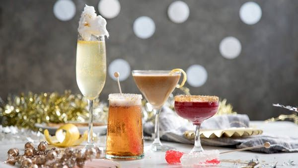 Recipe with video instructions: Ring in the new year in style with four colorful cocktails featuring champagne, prosecco, vodka, and gin. Ingredients: Lemon wedges, Gold sanding sugar, White sanding sugar, Pinch salt, 1 1/2 ounces vodka, 1 teaspoon edible pearl dust, 1 ounce sour mix, 1/2 ounce Viniq Ruby, 1/2 ounce pomegranate juice