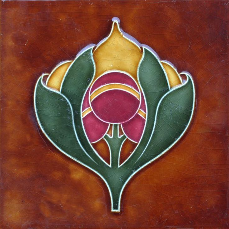 An Art Nouveau polychrome tube line tile with stylised flower head and leaf design on a brown ground. Condition: some...