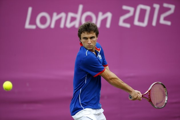 Day Three - JULY 30: Gilles Simon of France plays a backhand during the Men's Singles Tennis match against Grigor Dimitrov of Bulgaria on Day 3 of the London 2012 Olympic Games at the All England Lawn Tennis and Croquet Club in Wimbledon on July 30, 2012 in London, England. (Photo by Jamie Squire/Getty Images)