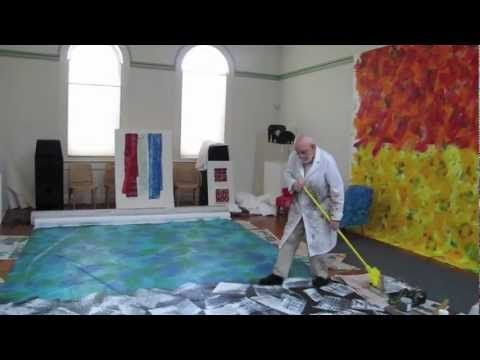 Eril Carl painting a large mural with a broom - looks like the paper he uses in his collages