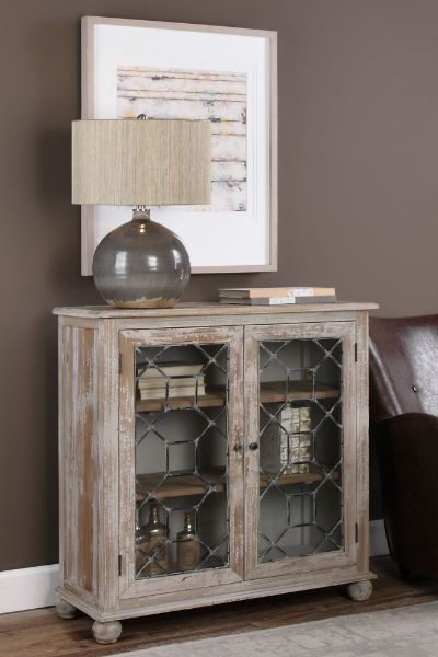 Inspired by the beautiful leaded glass windows found in England's stately Tudor homes, the Wiltshire cabinet combines a smaller footprint with ample storage space, making it an excellent choice for rooms both large and small. Versatile enough to work as a media cabinet, for storing books or showcasing curios, it's constructed of reclaimed pine with an antique white finish that's heavily distressed for a wonderfully weathered patina. Our Wiltshire Two-Door cabinet makes a beautiful addition.