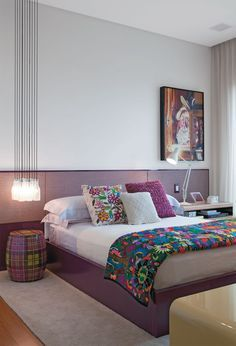 Um conjunto de luminárias da holandesa Droog Design (Decameron) cai como um cacho de luz sobre o garden seat (Conceito Firma Casa). O tecido da Micasa forra o painel, que corre por toda a parede da cabeceira. Sobre a roupa de cama da Casa Almeida, manta mexicana.