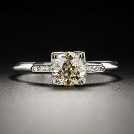 An exotic twist on a traditional vintage engagement ring. In place of a colorless, pallid center stone, this platinum solitaire glistens and glows with a light cognac, or champagne-colored European-cut diamond, weighing 1.11 carats. The scintillating stone is presented in a square box setting between slender rows of small twinkling single-cut diamonds leading to a sleek knife-edge ring shank. Currently ring size 7 3/4.