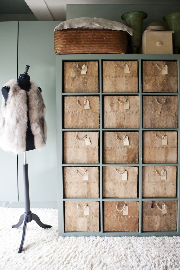 Bedroom storage: an Ikea Expedit roomdivider painted the same shade as the wall, and filled with labeled drawer-boxes... a very chique effect for little money. The home of interior decorator Madelon Oudshoorn Spaargaren.