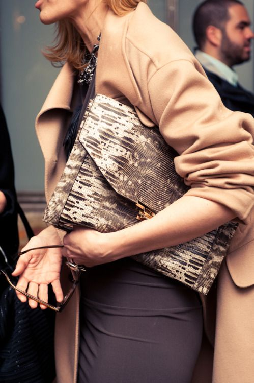 A camel coat and lizard clutch