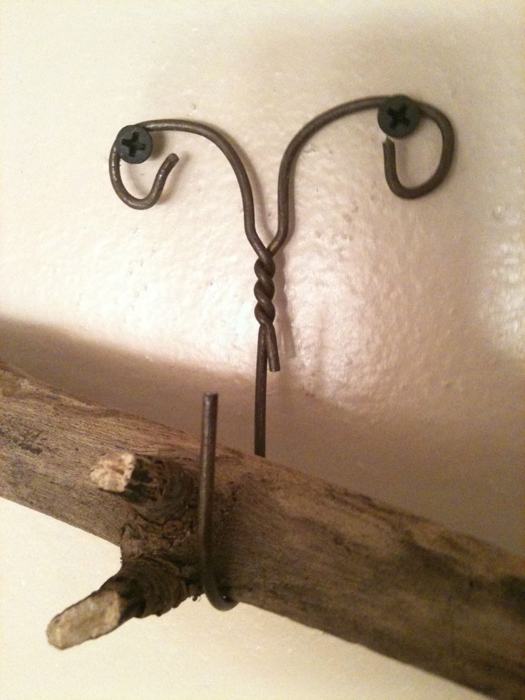 Homemade hook for hanging light objects made from a metal cloths hanger. Or turn it sideways to hold curtains back. love this idea!  but i just threw away old hangers!