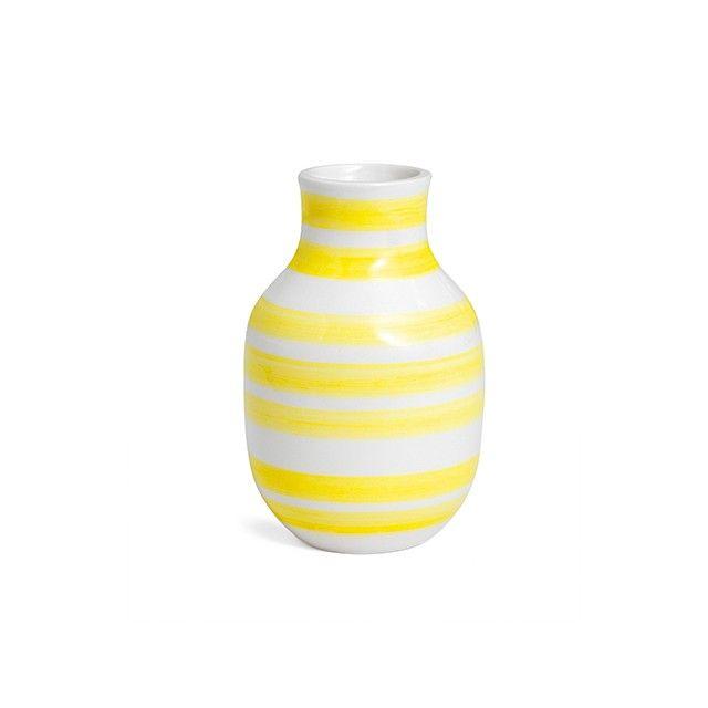 Omaggio Vase Solskinsgul Lille   Den lille buttede Omaggio-vase med de solskinsgule striber bidrager med et lyst og levende farveunivers til boligen. De klare gule striber er sirligt malet på vasens dybhvide farve, og stråler yndigt gennem den transparente glasur. Pynt vasen med et par enkelte trommestik-blomster og lad de gule nuancer bringe lys og glæde til den minimalistiske boligindretning, eller fungere som et supplement til den mere farverige indretning.
