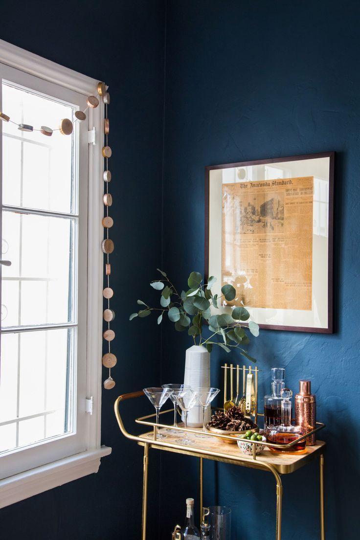 Dark blue walls, window with Pom Pom streamer, bar cart and art work