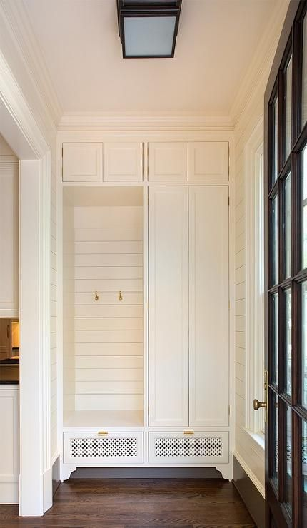 Small, well design small cottage mudroom features built in white cabinets framing an open locker fitted with a white shiplap backsplash and brass hooks mounted over white grill shoe drawers finished with brass pulls.