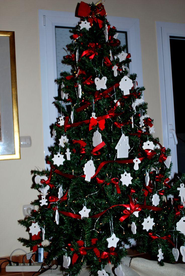 Χριστουγεννιάτικο δέντρο στολισμένο με χειροποίητα στολίδια από ζυμάρι σε χρώμα λευκό με κόκκινες κορδέλες.
