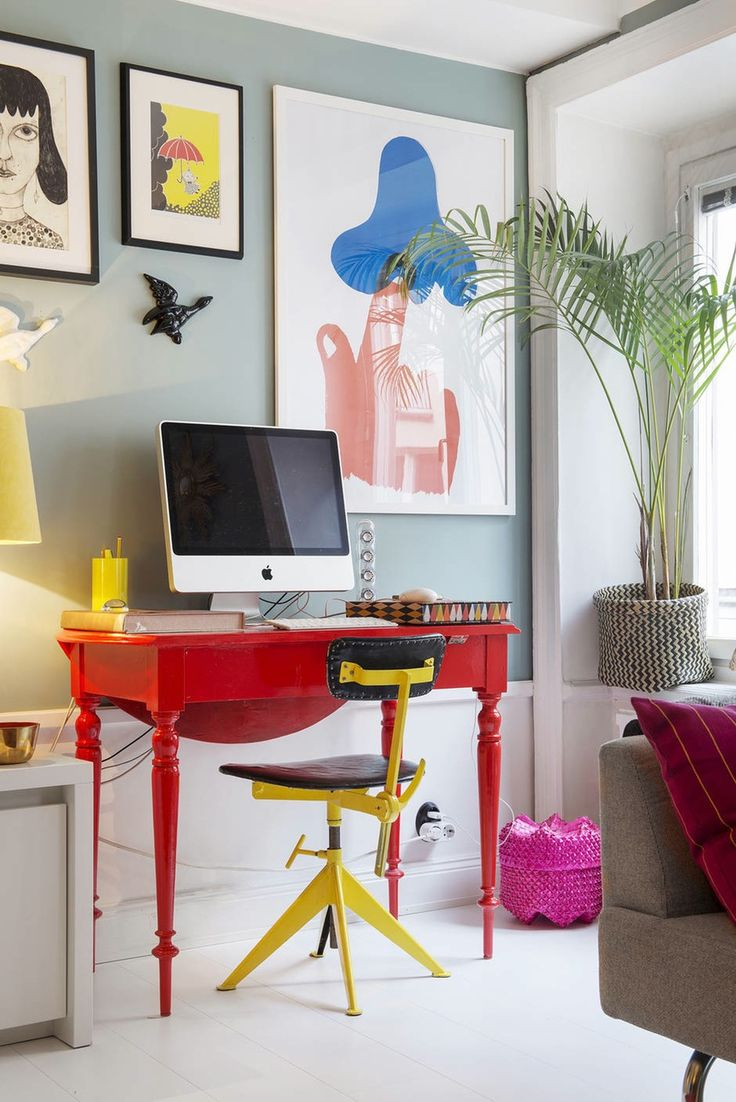 Small and colorful home office with a red desk and a yellow office chair.