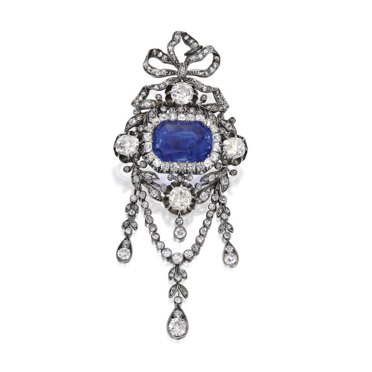Gold, Silver, Sapphire and Diamond Brooch. Centering a buff-top emerald-cut sapphire weighing 16.96 carats, within a bow motif frame set with numerous old mine and single-cut diamonds weighing approx 6.85 carats; circa 1890.