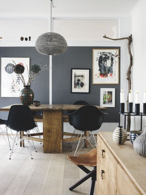 Rustic Modern Chic. Cocoon-like hanging light, gorgeous gray wall, placement of artwork, combination of rustic table and modern plastic chairs, repeated black accents.
