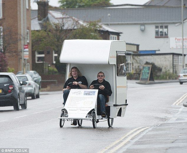 Tiny vehicle: Andy Saunders and work colleague Martin Ford ride in the van. It cost £1,000 to build and doesnt have to be registered to go on the roads because it is officially a bicycle