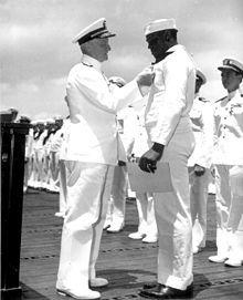Dorie Miller, hero of Pearl Harbor, receiving the Navy Cross from Chester Nimitz, May 27, 1942.