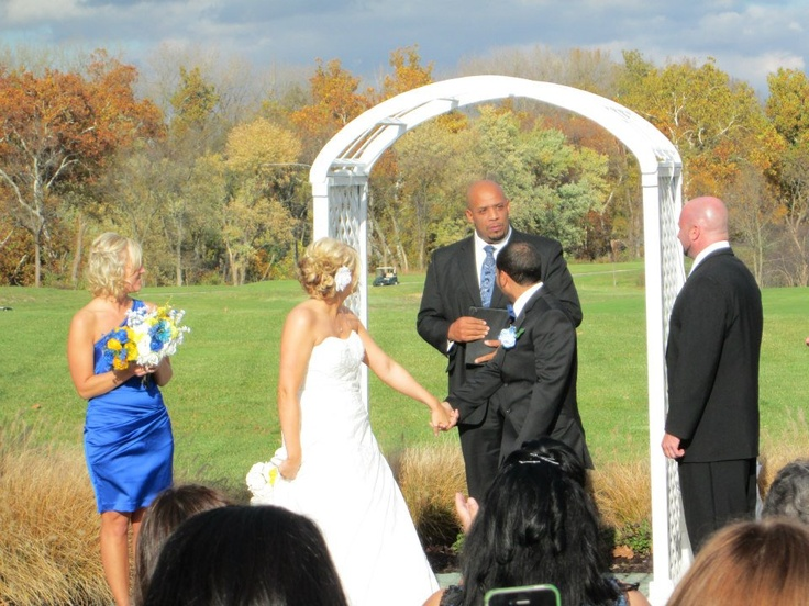 Outdoor wedding ceremony. Beautiful fall wedding on golf course. Prairie View Golf Club. Blue, white, and yellow wedding colors. White wedding arch.