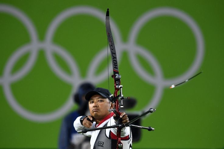 Canadian archer Crispin Duenas out in the rain.  High school physics teacher/Olympic archer Crispin Duenas was knocked out of competition on Wednesday in the round of 16 by American Zach Garrett. Here he is Duenas before the rain set in - Rio Olympics Day 5 Aug 10 2016 highlights Crispin Duenas archery