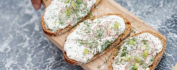 Mix  de makreel met de plattekaas. Klop  de slagroom even op en meng onder de makreelmousse. Breng  op smaak met citroensap, mierikswortel, peper en zout. Besmeer  een boterham met de mousse en werk af met wat fijne schijfjes radijs en  dillesnippers.