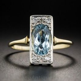 Something darling and refreshingly different in a modestly proprtioned (for a dinner ring) jewel from Edwardian England. The simple geometric design is delicately rendered in platinum over 18K gold and features a cool blue, faceted, elongated oval aquamarine embellished north and south with a trio of small glittering old mine-cut diamonds. 9/16 inch long and lovely. Currently ring size 7.