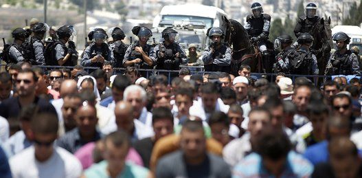 Beautiful Ramadan Photos From Around The World -Israeli police stand guard as Muslim men pray in the middle of a street outside the Old City in East Jerusalem on July 4, 2014, during the first Friday prayer of the holy fasting month of Ramadan. Israeli authorities closed the access to the Al-Aqsa Mosque for Palestinians men under 50-years-old, due tensions in West Bank