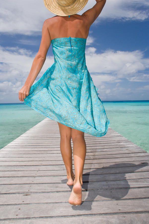 Woman sarong resort. Beautiful woman walking down tropical resort pier in sarong…