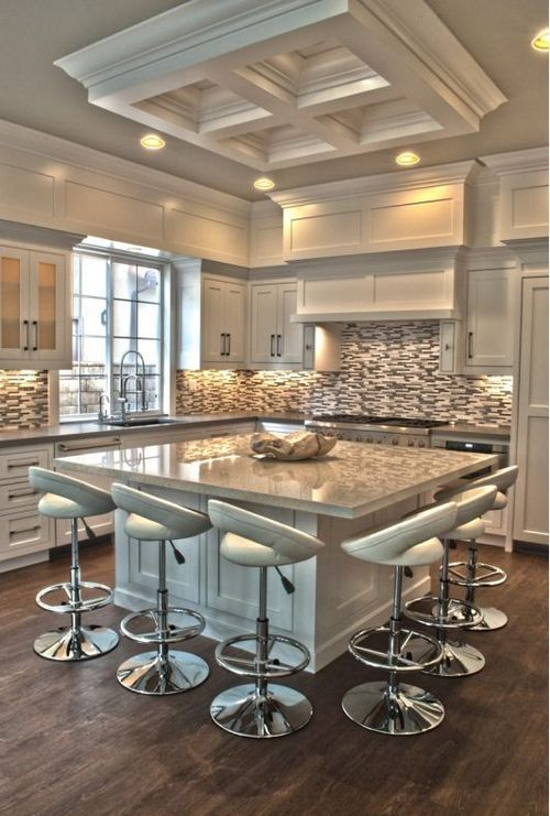 A great kitchen in soft white/grey colors. A large island with plenty of seating and a really fun multicolored backsplash. Even though it has a small window it feels lighter and brighter because of the colors selected.