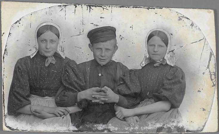 Twee meisjes en een jongen in Huizer streekdracht. De meisjes dragen een gehaakte 'pikmuts' (pikken is het Huizer woord voor haken). Dergelijke pikmutsen werden gedragen door meisjes tot hun 14e-15e levensjaar en als doordeweekse muts voor volwassen vrouwen. #NoordHolland #Huizen #pikmuts