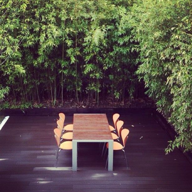 Bamboo terrace with STUA's Deneb table in teak & orange Globus chairs. (Project by www.dopico.info)