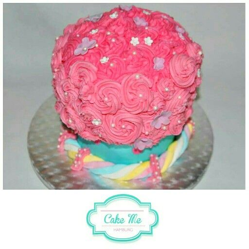 A gigant cupcake cake with pink buttercream and blue bottom. Inside two tired cake. Great for a girl 6th birthday