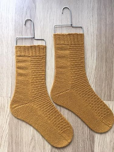 This cuff down sock pattern features a 56, 64 and 72 stitch sock size. A simple texture stitch is used, which is easily memorizable. This pattern uses a short row heel and a rounded toe.