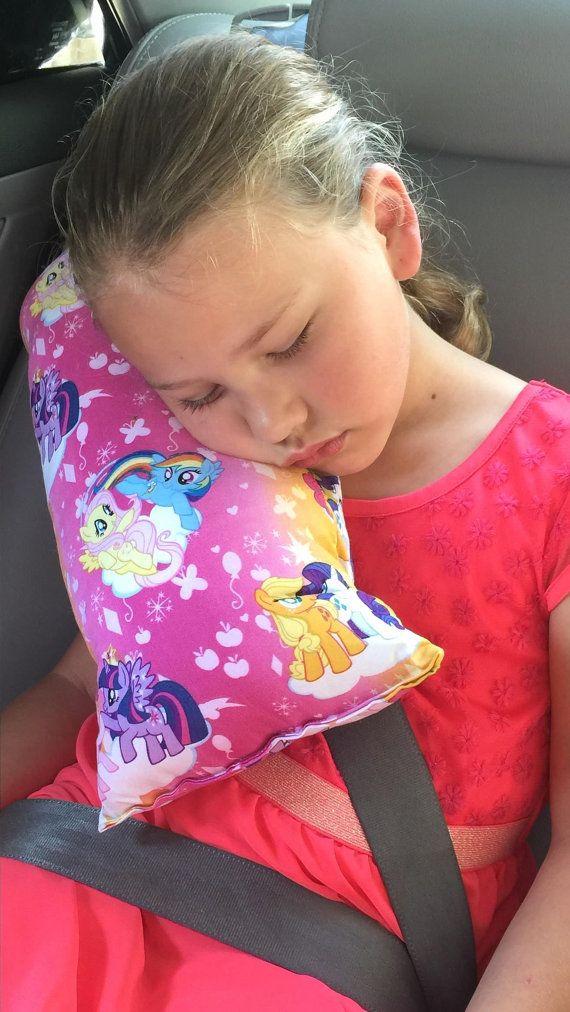 Una almohada de gran cinturón de seguridad para los viajes de largo/corto. Esta almohada de viaje del cinturón de seguridad hace esos viajes largo camino mucho más cómodo y divertido para su hijo!  Esta almohadilla de cinturón de seguridad los lazos en el frente del cinturón de seguridad con la cinta por lo que es fácil de usar en los niños que utilizan el cinturón del arnés del hombro.  Almohada mide 18 x 9 pulgadas. Hecho con tela de My Little Pony y es lavable.