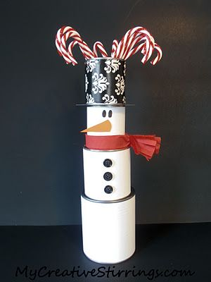 This fancy centerpiece is made primarily of un-opened food cans wrapped in paper.  The hat is an open food can covered in wrapping paper with candy cane ornaments coming out of the top.  The scarf is made using a red napkin.