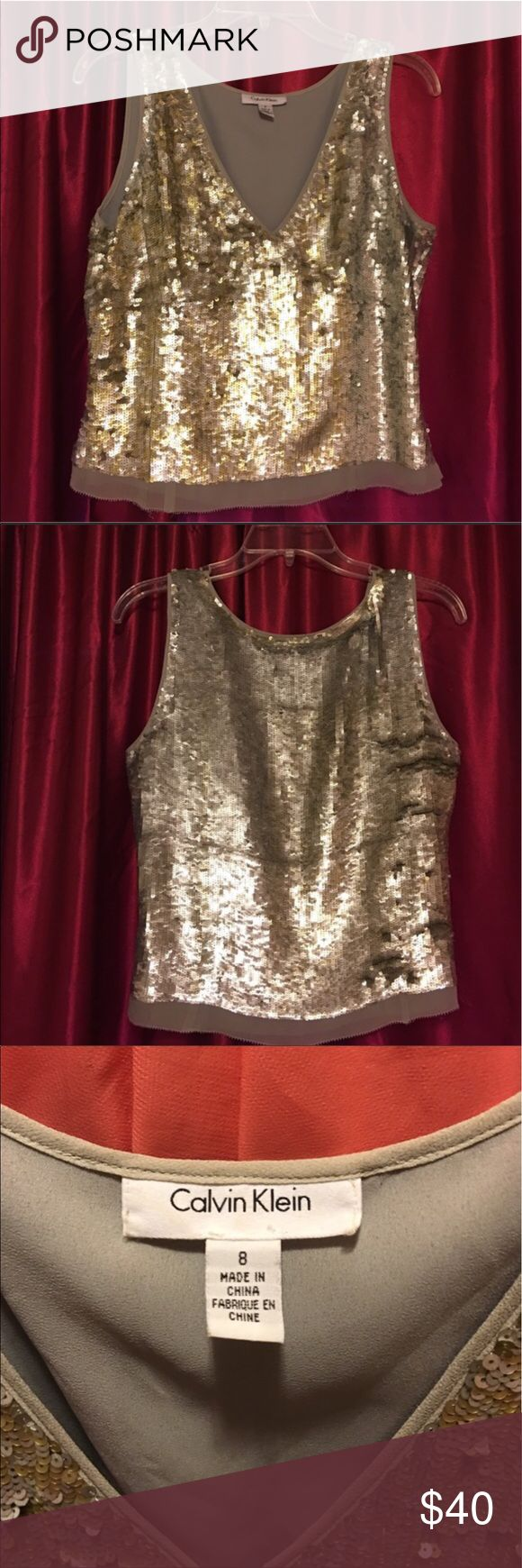 """🎉HP 11/05🎉 NWOT Calvin Klein sequin top Calvin Klein sequin top. Never worn. 20"""" from shoulder to hem. A dazzling array of silver and gold sequins. 100% silk outer shell that hosts sequins and polyester inner shell. Size 8. There are a couple spots where the sequin threading has come loose letting several sequins fall off. Will post pictures later. Original price $350! Bought for NYE but never wore it. Calvin Klein Collection Tops Blouses"""