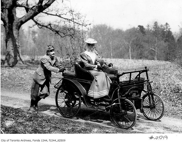 A man pushing a woman in an early automobile, Toronto, c. 1900. #vintage #Canada #cars