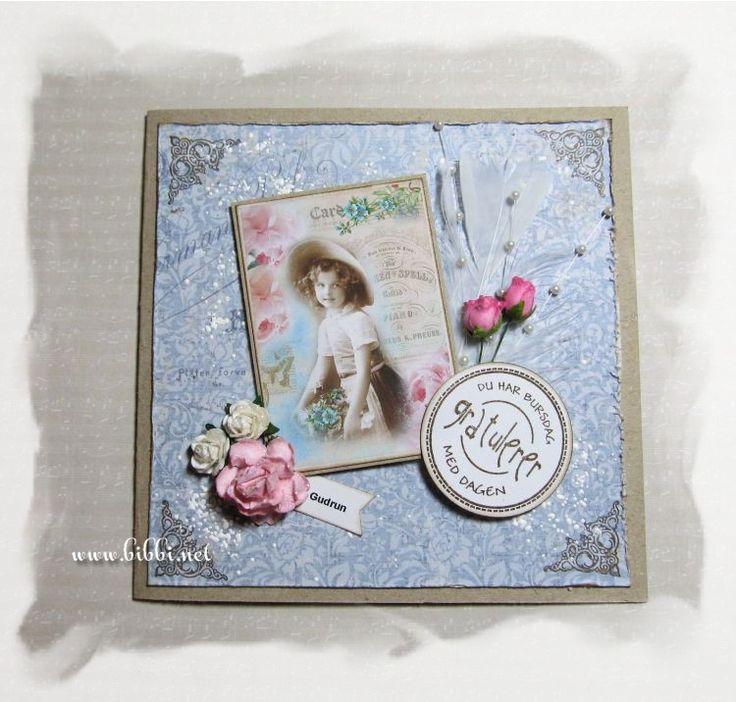 Et bursdagskort i kraft og Maja Design. Pyntet med fjær, perlestrå, blomster, hjørnetrykk og en tekst fra Kreativ Hobby. Kantene er rufse...