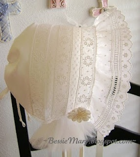 This bonnet is so simple, but so sweet! Construction incorporates the basics of heirloom sewing by machine: joining lengths of lace and Swiss entredeux insertion with a tiny zig zag stitch. A ruffle of wide Swiss edging, rolled and whipped to the fancy band, frames the baby's face. A narrow piece of Swiss Nelona is rolled and whipped to the back. It is then gathered with ribbon run through a narrow casing.