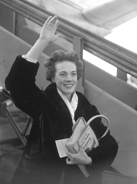 Carrying a map of Switzerland Julie Andrews waves goodbye at London Airport as she boards a plane for Zurich on her way for a holiday at Klosters She...