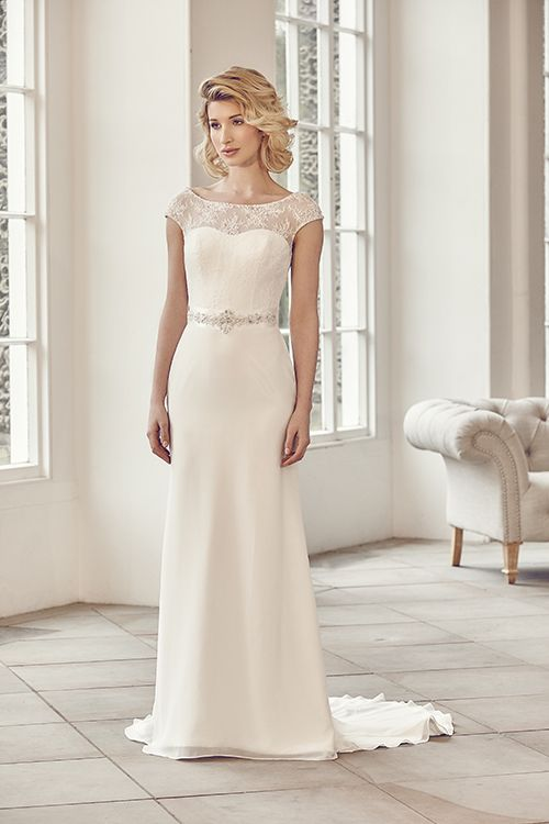 A sheath style bateau neckline gown with lace, chiffon and detailed belt. <strong>Size: </strong>8 – 30 <strong>Colour: </strong>Ivory <strong>Fabric:</strong> Lace, Chiffon <strong>Style:</strong> Sheath <strong>Neckline:</strong> Bateau <strong>Laced or Zipped: </strong>Zipped