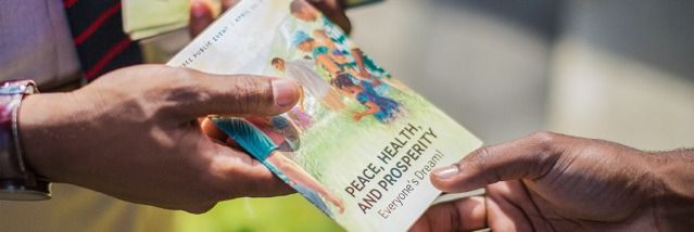 Uma Testemunha de Jeová entregando o convite da Celebração para uma pessoa