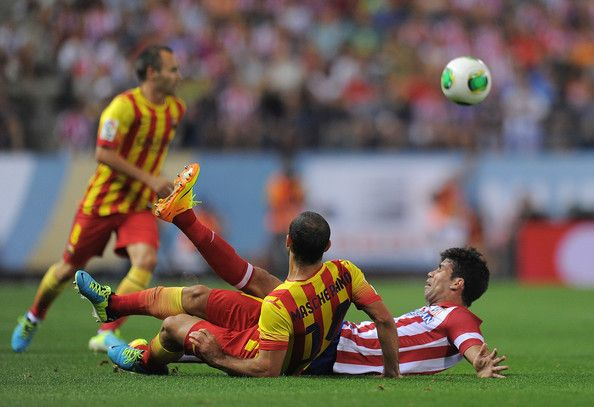 Diego Costa (R) of Atletico de Madrid clashes with Javier Mascherano of Barcelona during the Spanish Super Cup first leg match between Atletico de Madrid and Barcelona at Vicente Calderon Stadium on August 21, 2013 in Madrid, Spain.