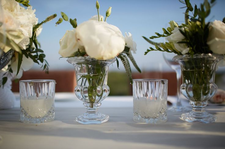 Smaller crystal vases with white peonies to fill up the table fashionably.