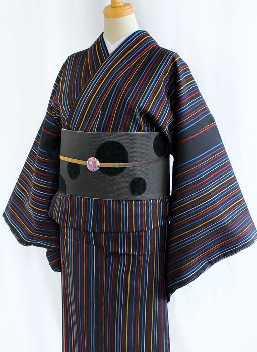 《今日の着物コーディネート》9月に入り一気に秋めいてきましたね(^-^)京都きものマートでは銘仙の着物を始め続々と新作が登場しています!本日は織り込まれたカラフルな縞がおしゃれ感たっぷりな新作のきものをご紹介です。黒地にスッキリとした縦のストライプに大きめドットの帯を合わせてモダンな印象に。陶器の帯留めをアクセントにしました。