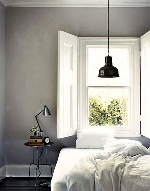 Bedroom with grey walls, crisp white linen bedding and black lamp