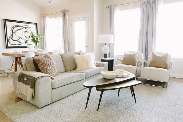 Bright white living room with a neutral sofa, matching armchairs and layered coffee tables