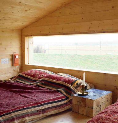 Rustic timber bohemian bedroom with a large window enabling views to a rural landscape. Earthy linen & rustic side table comprised of timber cubes. Love!