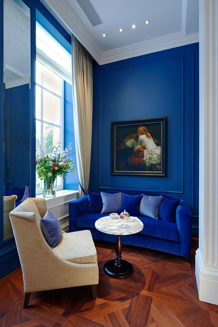 Синий бархат диван против голубой стены с помощью журнала Vogue